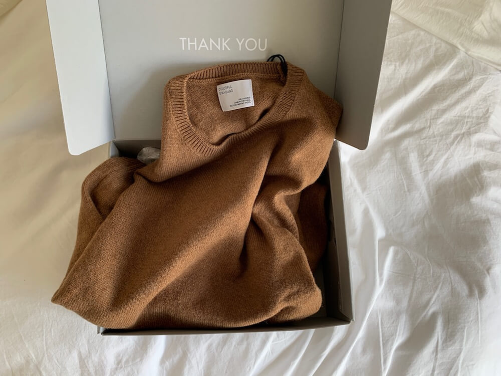Colorful Standard Recycled merino wool sweater in sahara brown pictured in box